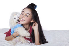 Woman relaxing on bed with dog. Beautiful woman with long hair, relaxing on the bed while hugging a maltese dog Stock Photography