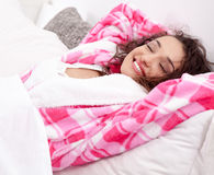 Woman relaxing in bed lying with her eyes closed and arms stret Royalty Free Stock Photography