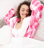 Woman relaxing in bed lying with her eyes closed and arms stretc Stock Image