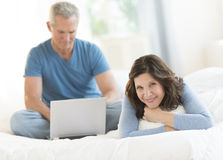 Woman Relaxing In Bed While Man Using Laptop At Home Royalty Free Stock Photos
