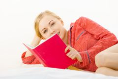 Woman relaxing in bed reading book Stock Photos