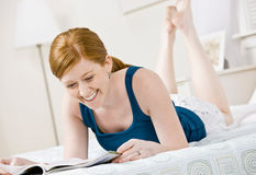 Woman relaxing in bed and reading magazine Royalty Free Stock Photography