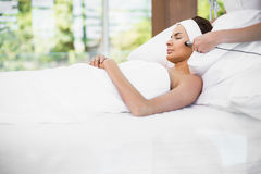 Woman relaxing on bed while receiving facial massage Stock Photography