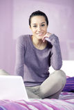 Woman relaxing in bed while using laptop Stock Images