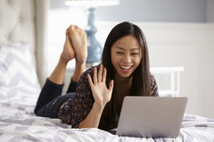 Woman Relaxing On Bed Using Laptop Computer For Video Call Royalty Free Stock Images