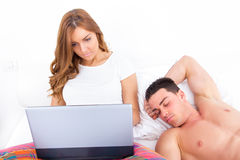 Woman relaxing in bed using laptop while husband is sleeping Royalty Free Stock Photo