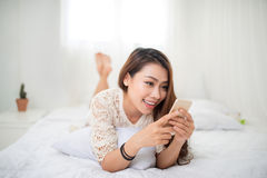 Woman Relaxing in bed and using mobile phone, relaxing in her li Stock Photography