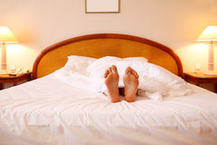 Woman relaxing on bed with white sheets Stock Photography