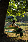 Woman relaxing on a bench Stock Photography