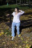 Woman relaxing on the bench in autumn Royalty Free Stock Image