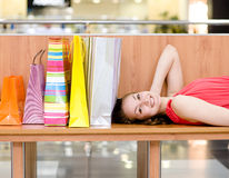 Woman relaxing on bench inside shopping center Stock Photos