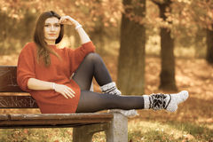Woman relaxing on bench. Nature outdoor relax leisure scenery concept. Redhead lady chilling on bench. Young elegant girl sitting in autumnal park Royalty Free Stock Images