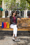 Woman relaxing in bench with shopping bags vertical Royalty Free Stock Image