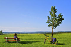 Woman Relaxing on Bicycle Tour, Bavaria. Woman relaxing on a bench with a nice view of a bavarian landscape (near Marloffstein, Franken, Germany Royalty Free Stock Image