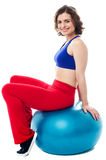 Woman relaxing on big exercise ball after workout Stock Photo