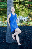 Woman relaxing black sand beach Hawaii. Bald woman in blue tropical dress relaxes against a palm tree in the shade at the Punaluu black sand beach on the Big Stock Photos