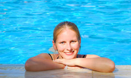 Woman relaxing in blue outdoor swimming waterpool Royalty Free Stock Photos