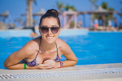 Woman relaxing in blue swimming pool Royalty Free Stock Photography