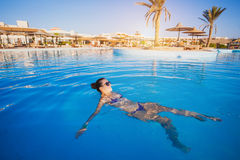 Woman relaxing in blue swimming pool Royalty Free Stock Images