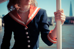Woman relaxing on boat on the Thames. A young woman in a sailor outfit is relaxing on a boat on the Thames in London, England Stock Photography