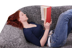 Woman relaxing with book on couch Stock Photos