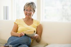 Woman relaxing with book in living room Royalty Free Stock Photos