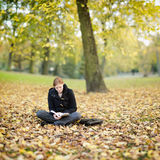 Woman Relaxing with a Book in a Park Stock Photos