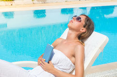 Woman relaxing with a book by the pool Royalty Free Stock Images