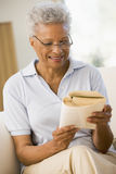 Woman relaxing with a book and smiling Royalty Free Stock Photography