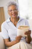 Woman relaxing with a book and smiling Royalty Free Stock Images