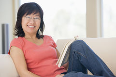 Woman relaxing with a book and smiling Royalty Free Stock Photos