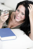 Woman relaxing with a book and wine Stock Photography