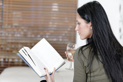 Woman relaxing with a book and wine Stock Image