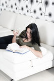 Woman relaxing with a book and wine Stock Images