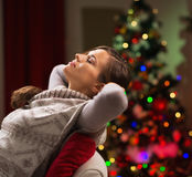 Woman relaxing on chair in front of Christmas tree Royalty Free Stock Image