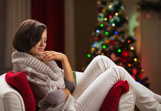 Woman relaxing on chair in front of Christmas tree Stock Photo