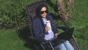 Woman relaxing on chair in garden. In summer day stock video