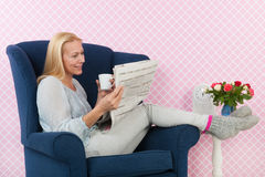 Woman relaxing in chair reading newspapers. Woman relaxing with newspapers in living room Royalty Free Stock Photo