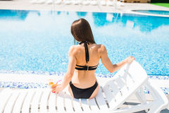Woman relaxing on chaise longue with cocktail rear view. Summer time Royalty Free Stock Image