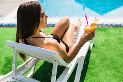 Woman relaxing on chaise longue with cocktail. Summer time Stock Photo