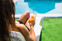 Woman relaxing on chaise longue with cocktail. Summer time Stock Images