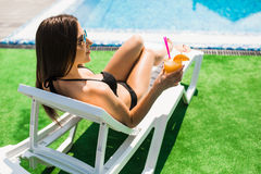 Woman relaxing on chaise longue with cocktail. Summer time Stock Image