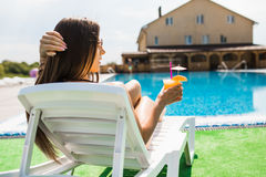 Woman relaxing on chaise longue with cocktail. Summer time Royalty Free Stock Images