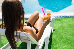 Woman relaxing on chaise longue with cocktail. Summer time Stock Photos