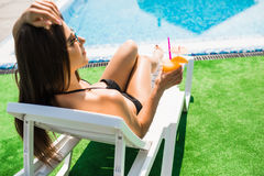 Woman relaxing on chaise longue with cocktail. Summer time Stock Photography