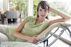 Woman Relaxing On Chaise Longue. Portrait of beautiful young woman relaxing on chaise longue at home stock image