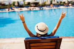 Rear view of Young beauty Woman in straw hat relaxing with hands up on chaise-lounge by the pool. Woman relaxing on chaise-lounge by the pool royalty free stock photography