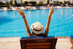 Rear view of Young beauty Woman in straw hat relaxing with hands up on chaise-lounge by the pool. Woman relaxing on chaise-lounge by the pool stock photography