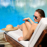 Woman relaxing at the poolside Royalty Free Stock Image