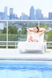 Woman relaxing at city pool Stock Images